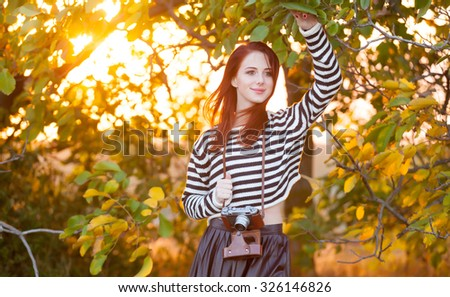 Woman with retro camera in autumn time outdoor