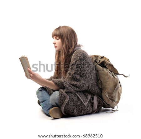 Woman with rucksack reading a book - stock photo