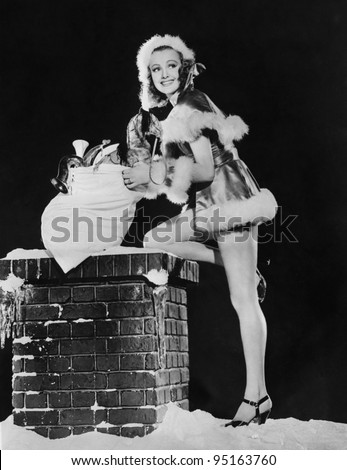 Woman with sack of Christmas gifs and snowy chimney - stock photo