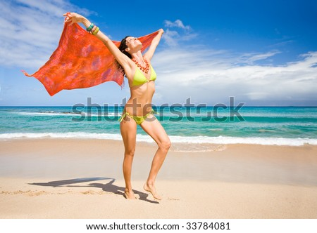 Woman with sarong on beach happy and carefree