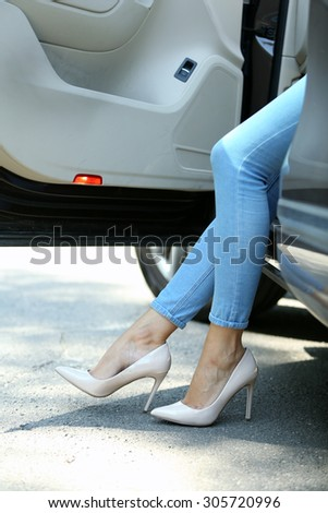 Woman with sexy legs in car, close-up