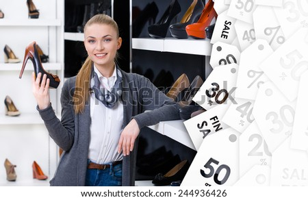 Woman with shoe in hand chooses stylish pumps looking at the shelves with numerous pumps on sale - stock photo