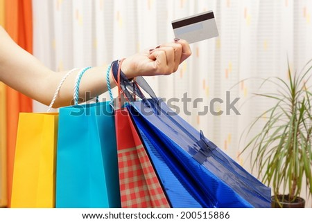 Woman with  shopping bags bought with a debit or credit card at home. Shopping from home concept - stock photo
