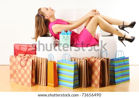 Woman with shopping bags having a rest on sofa - stock photo