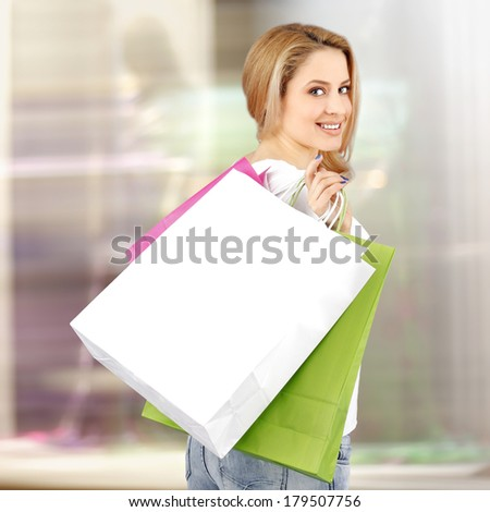 Woman with shopping bags in front of a window - stock photo