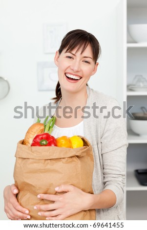 Woman with shopping bags in the kitchen at home - stock photo