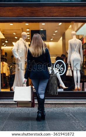 Woman with shopping bags looking at boutique showcase - stock photo
