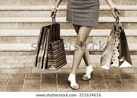 Woman with shopping bags on the mall steps - stock photo