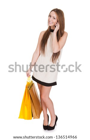 Woman With Shopping Bags Talking On Cell Phone Over White Background - stock photo