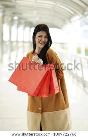 woman with shopping  bags walking and talking together. Great day for shopping. Young beautiful women with shopping bags  with smile while walking outdoor. Young female  doing shopping on streets.