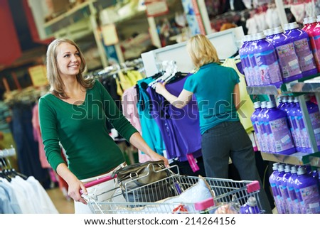 woman with shopping cart trolley in apparel clothes shop supermarket - stock photo