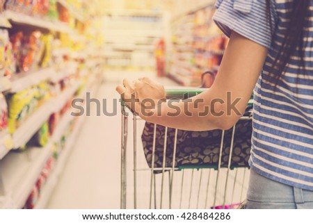 Woman with shopping cart. Vintage filter - stock photo