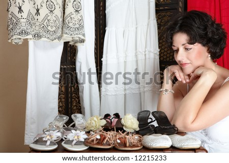 Woman with short brown hair sitting next to her shoe collection in her mid 30s, early 40s - stock photo