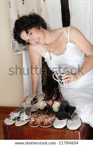 Woman with short brown hair sitting next to her shoe collection with cup a coffee and smiling, in her mid 30s, early 40s
