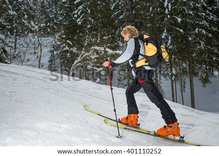 Woman with ski mountaineering uphill in the woods - stock photo