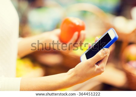 woman with smartphone and persimmon in market - stock photo