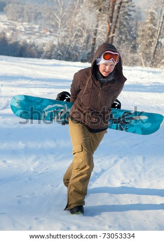 Woman with snowboard climbs up the hill