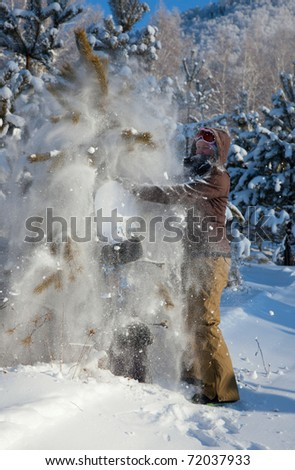 Woman with snowboard in the fir forest
