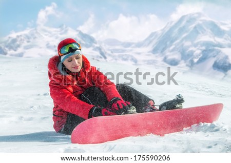 Woman with snowboard sitting in the snow  - stock photo