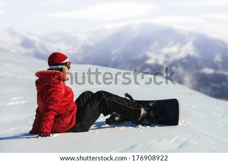 Woman with snowboard sitting in the snow, mountains in the background - stock photo