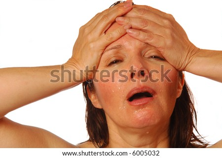 Woman with splitting headache holding hands on forehead - stock photo