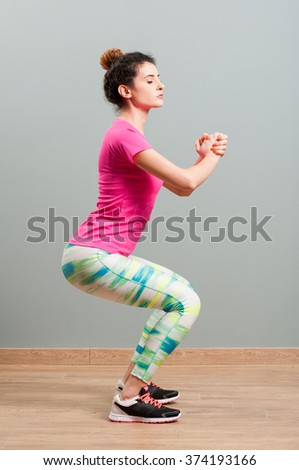 Woman with sportswear squatting and shaping her body as indoor activity concept - stock photo