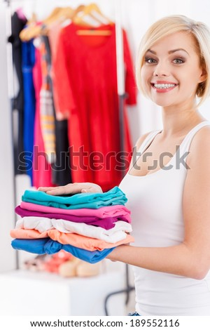 Woman with stack of clothes. Beautiful blond hair woman holding stack of multi colored clothes and smiling at camera - stock photo
