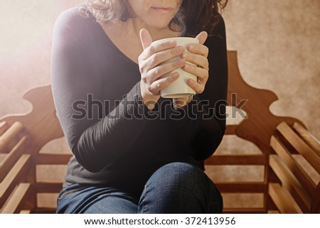 woman with steaming cup partial body
