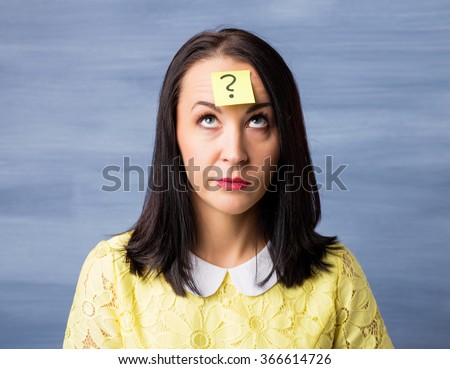 Woman with sticky note on her forehead looking up at question mark  - stock photo