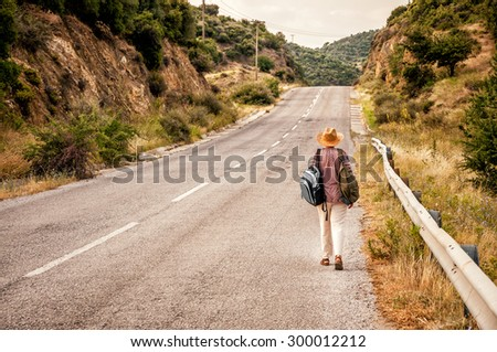 Woman with straw hat and two rucksacks on her back walking alone on the road during vacation in the Mediterranean - stock photo