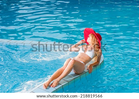 Woman with straw hat relaxing at the swimming pool - stock photo