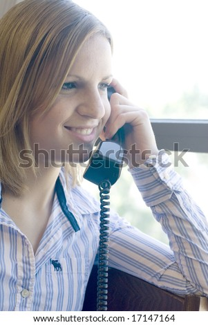 Woman with striped short smiling while holding a telephone receiver