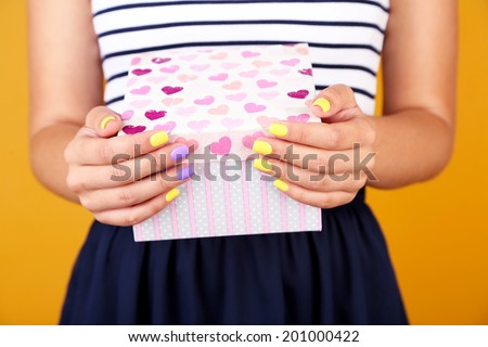 Woman with stylish colorful nails holding gift box, close-up, on color background