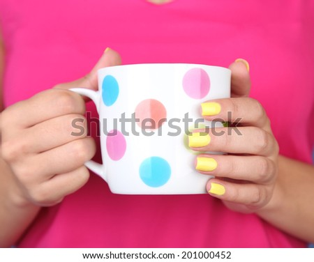 Woman with stylish colorful nails holding mug, close-up, on color background - stock photo