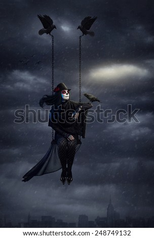 Woman with sugar skull makeup holding black crow and flying above the city at dark overcast sky with snowfall - stock photo