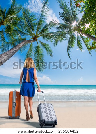 Woman with suitcase on the tropical beach - stock photo