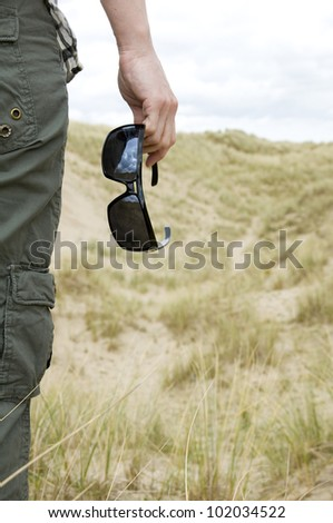 woman with sun glasses in sand dunes on vacation