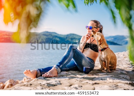 Woman with sunglasses wearing black bikini and jeans giving her dog cookies - stock photo