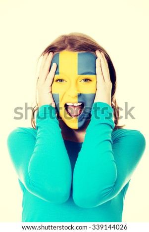 Woman with Sweden flag painted on face. - stock photo