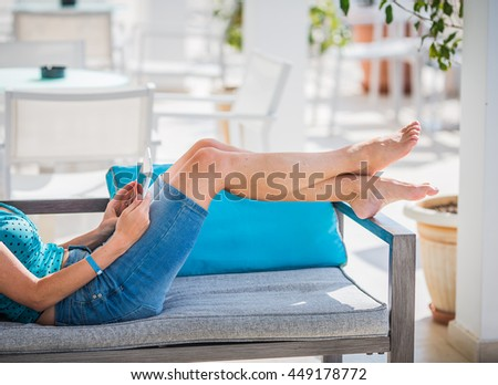 woman with tablet relaxing on the terrace in luxury hotel. - stock photo