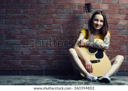 Woman with tattoo and guitar sitting on background on brick background - stock photo