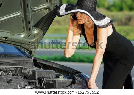 Woman with telephone near the broken car - stock photo