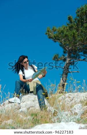 woman with the map in the mountains - stock photo