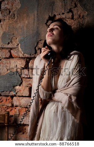 Woman with the old phone on the background of a brick wall. In a retro style - stock photo
