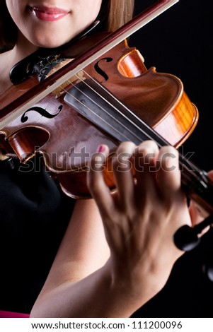 Woman with the violin over black background