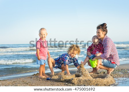 Woman with three children on the beach