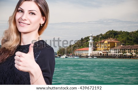 Woman with thumbs up on the beach background. - stock photo