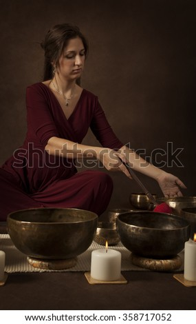 Woman with Tibetan singing bowl in front of brown background - stock photo