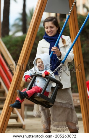 woman with  toddler on swings in autumn