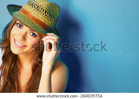 woman with toothy smile touching hat with fields . - stock photo